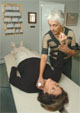 Chiropractor Laura Bomback tests patient Carol Lapointe using one of her test vials to see what effect it has.